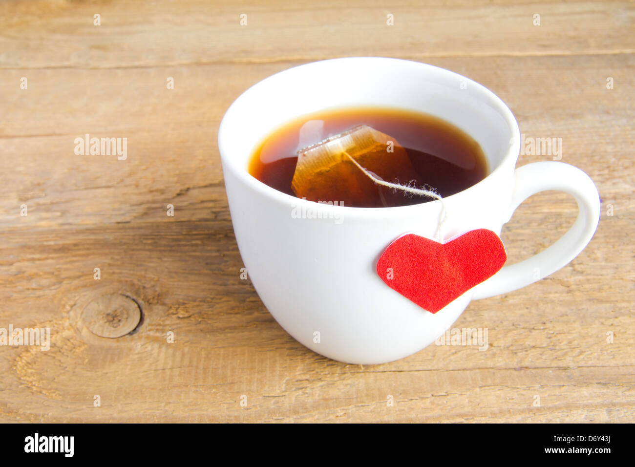 White Cup Of Tea With Red Heart Shaped Label On Teabag On Wooden