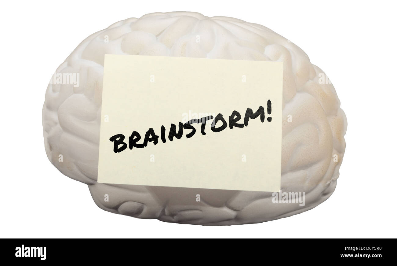 Post-it note with the word Brainstorm! on model of human brain. - Stock Image