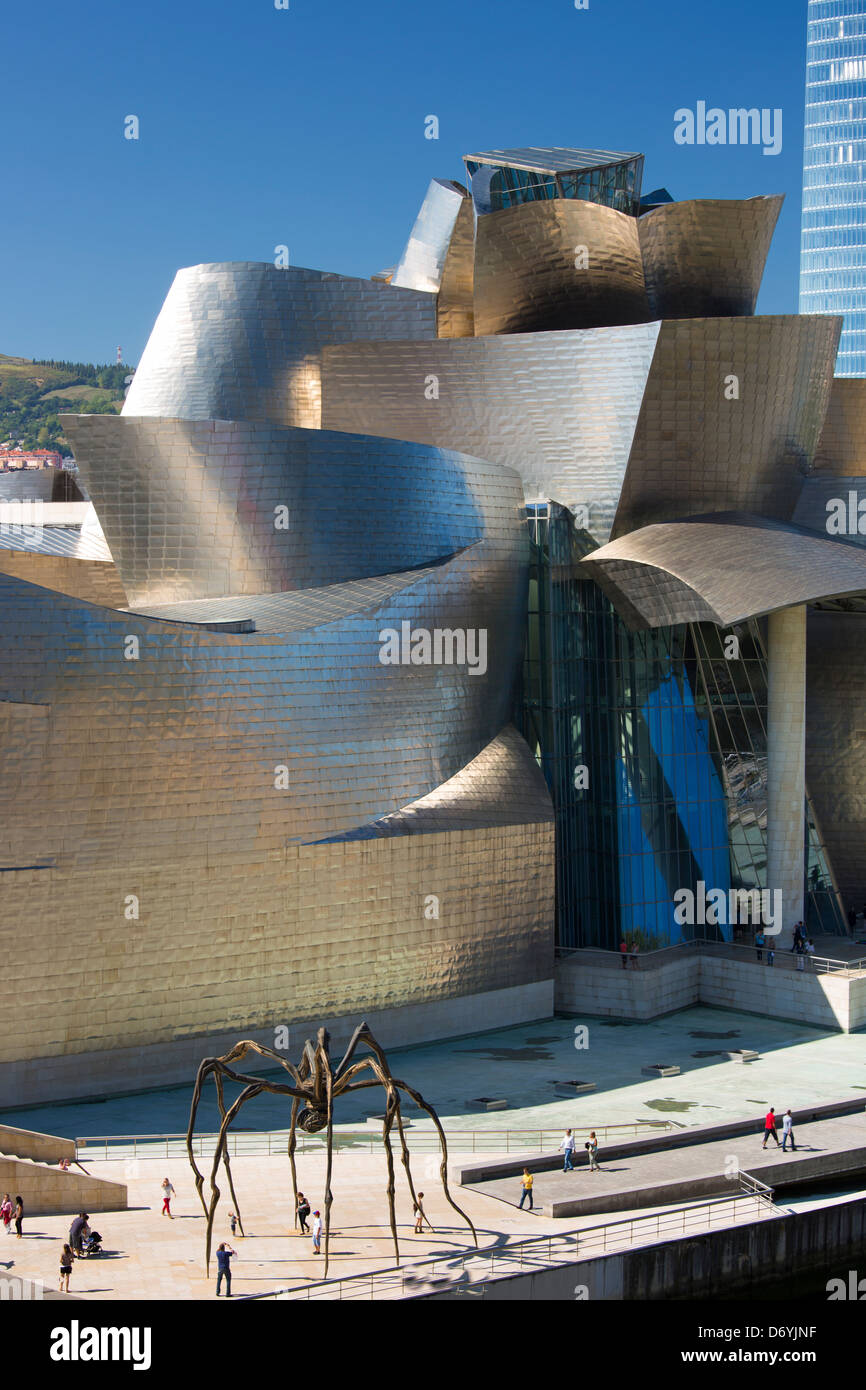 Tourists at Guggenheim Museum view giant bronze spider sculpture 'Maman' in Bilbao, Spain - Stock Image