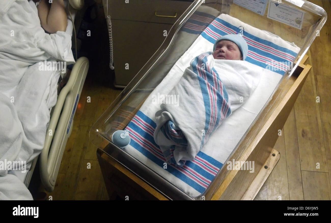 Caucasian newborn baby sleeping in bassinet Stock Photo