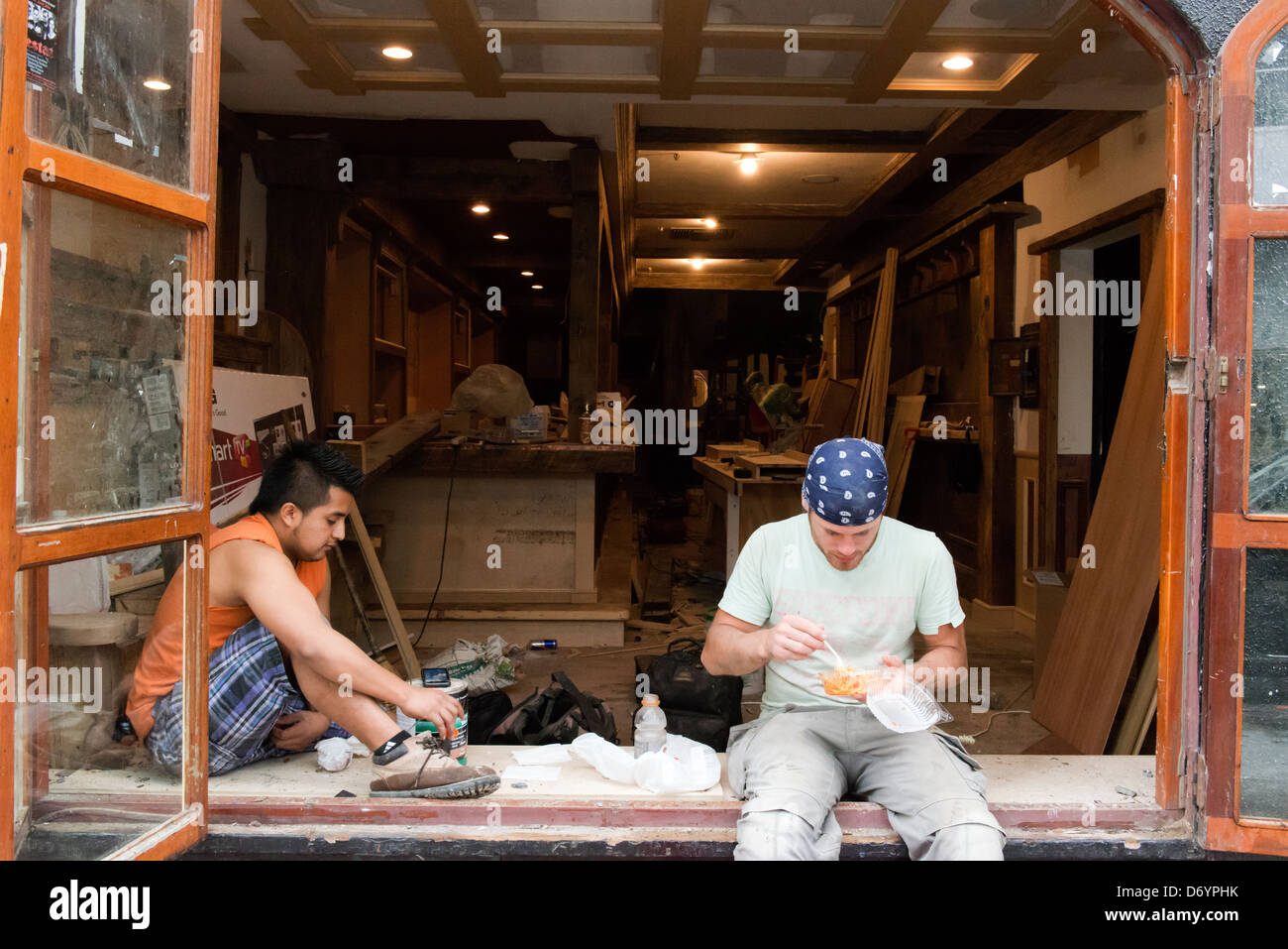 Tradesmen stop for lunch while working on a construction site in Lower Manhattan. - Stock Image