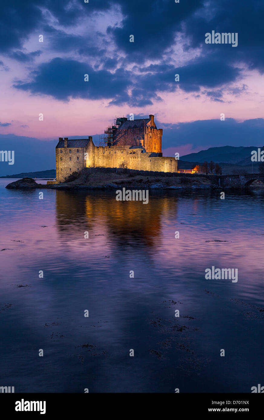 Eilean Donan Castle afte the sun has set, with the sky turned a magenta pink and the castle illuminated by floodlighting Stock Photo