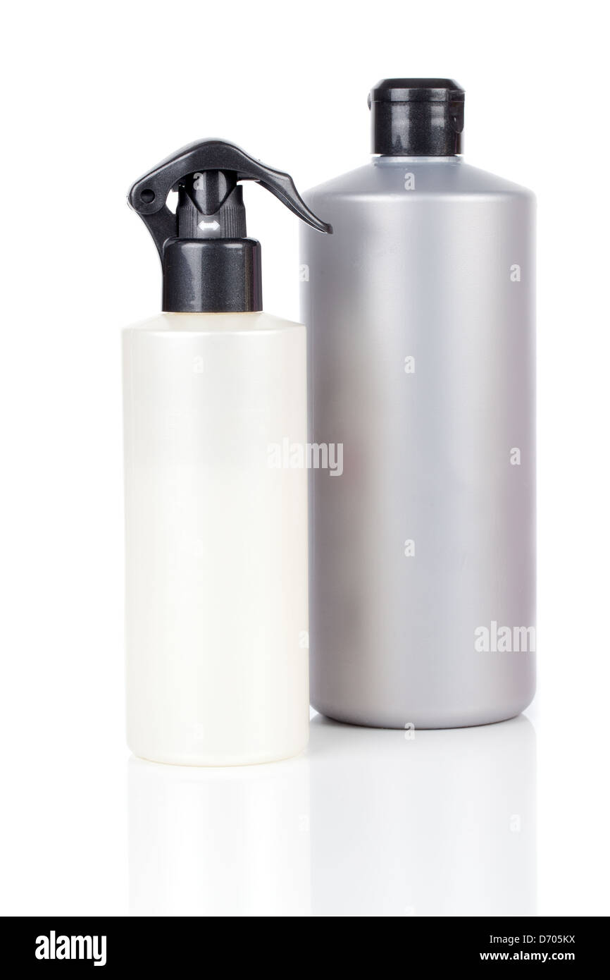 Two plastic bottles of hair care products, with soap or shampoo without label reflected on white background Stock Photo