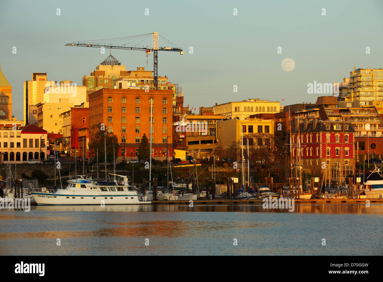 Full moon rising over Victoria skyline and Inner Harbor with construction crane on building-Victoria, British Columbia, - Stock Image