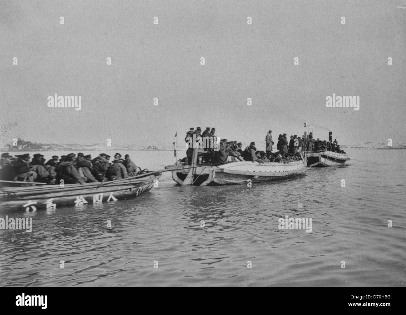 Steam launch carrying six over-crowded boat loads soldiers to landing, Chemulpo, Korea, during the Russo Japanese - Stock Image
