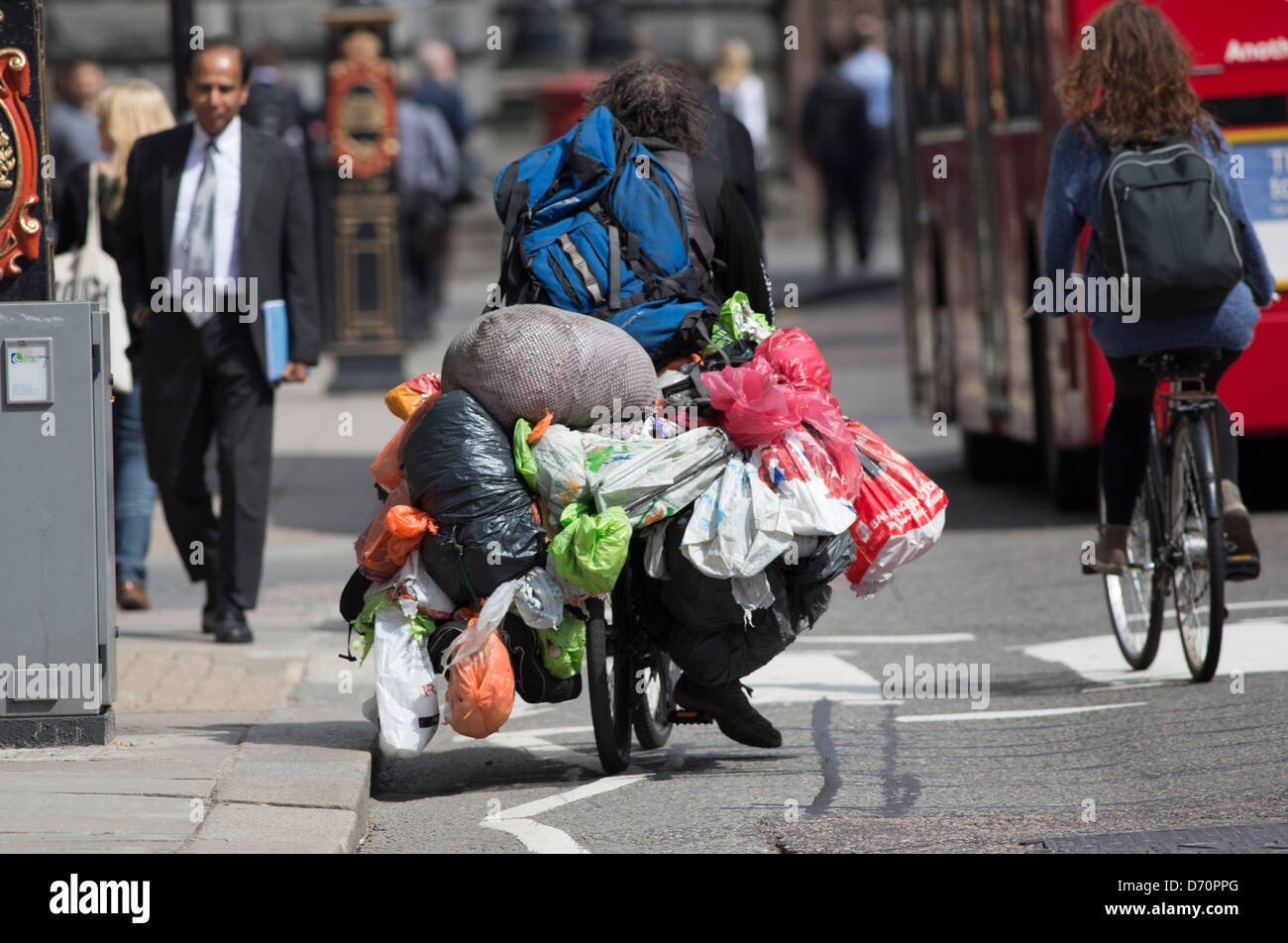 Tramp bag man bagman cycling through london weighed down with carrier bags - Stock Image