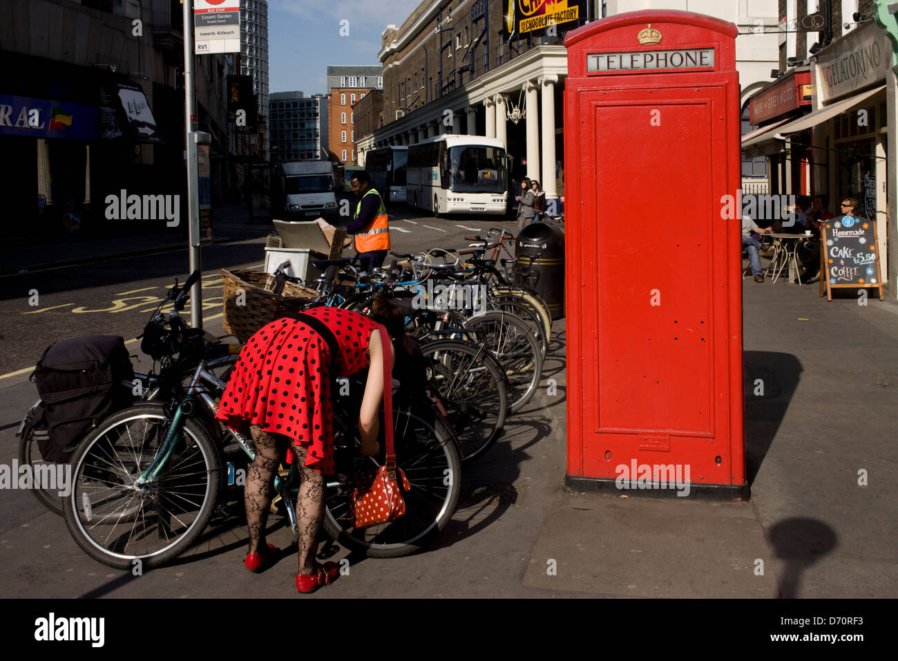 A lady wearing a red dress with black polka dots locks her bike near a red public telephone kiosk. - Stock Image