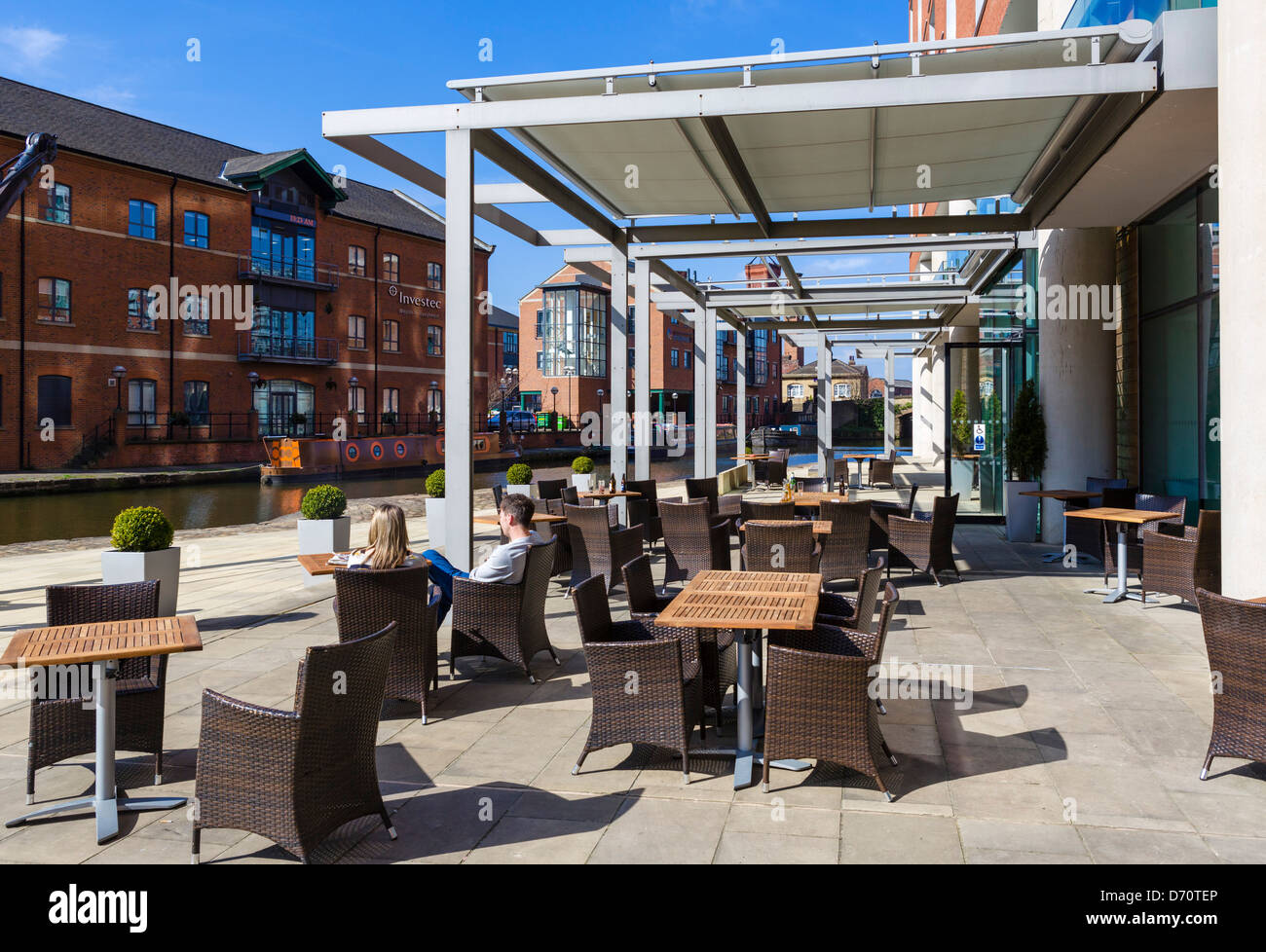 Couple siting on terrace of DoubleTree Hotel overlooking Leeds-Liverpool Canal, Granary Wharf, Leeds, West Yorkshire, - Stock Image