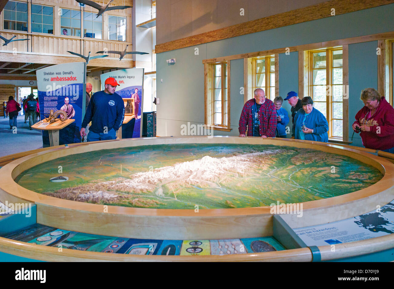 Tourists viewing a three dimensional topographic map at the Denali National Park Visitors Center, Denali National Stock Photo