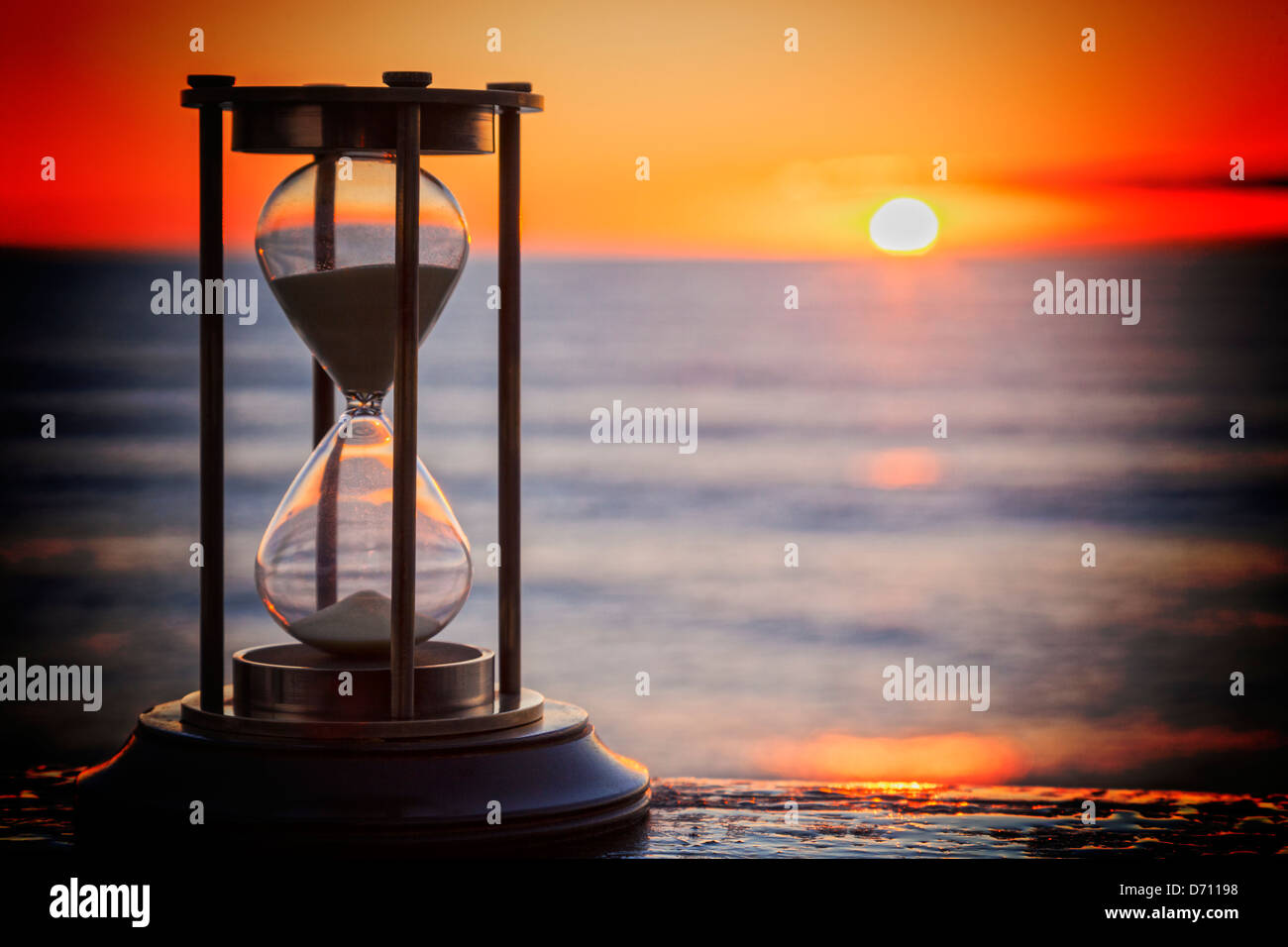 Sand Timer at Sunrise - Sand timer on a wooden ledge, looking out over a sunrise. - Stock Image