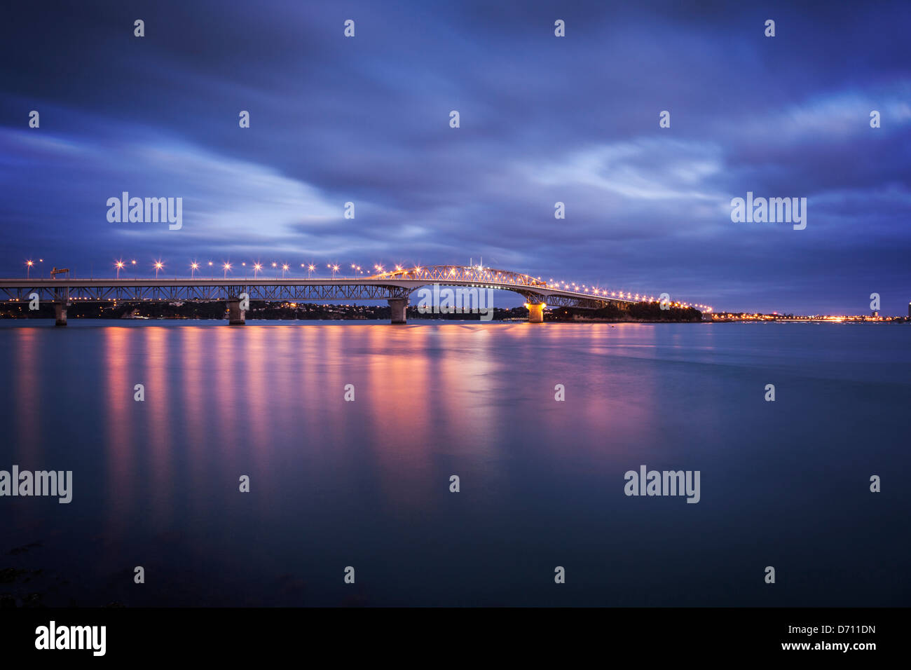 Auckland Harbour Bridge with its lights on at twilight. - Stock Image