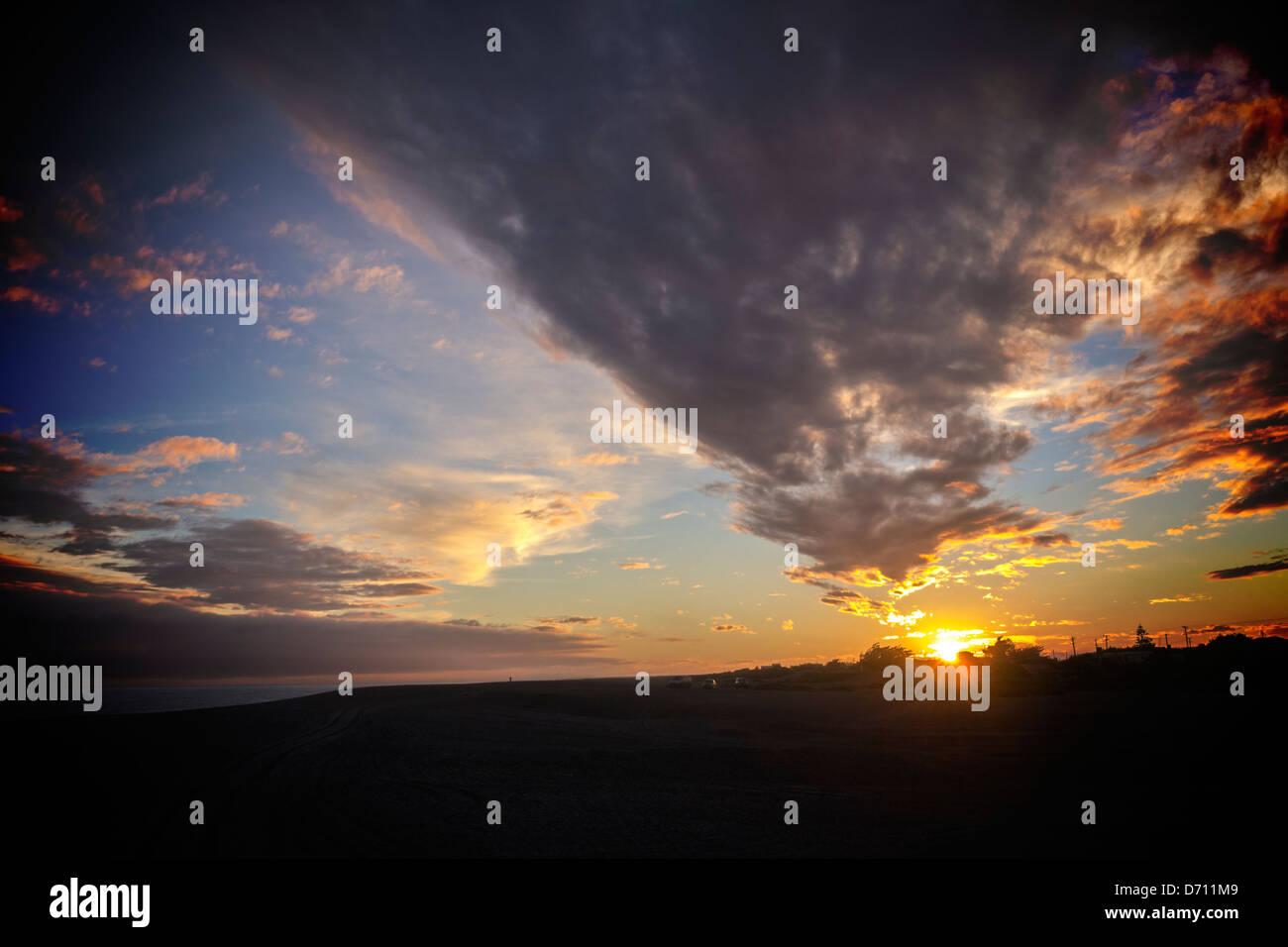 Sunset in Moody Sky - a dramatic sunset over a dark beach. - Stock Image