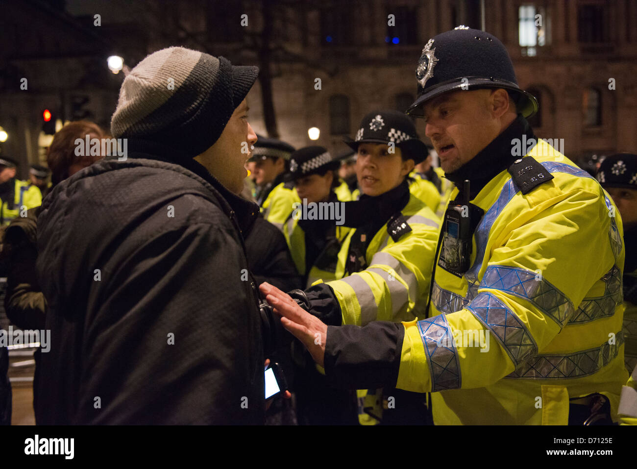 Metropolitan police try to calm down a protester who feels he is being detained against his will - Stock Image