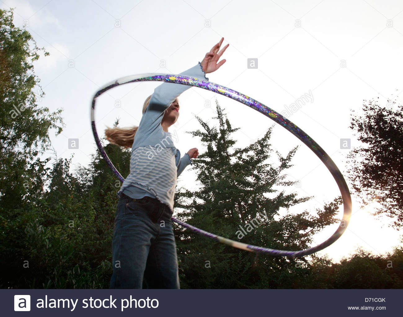 Low angle view of a girl playing with a hula hoop - Stock Image