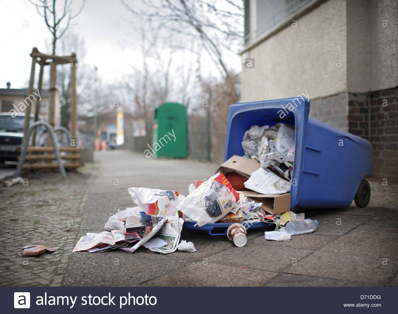 Fallen garbage bin in the street - Stock Image
