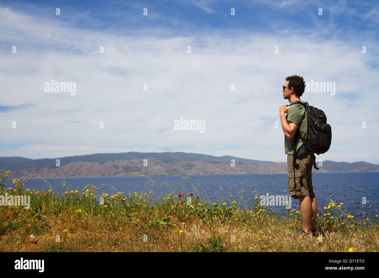 tourist backpacker looking forward, summer travel - Stock Image