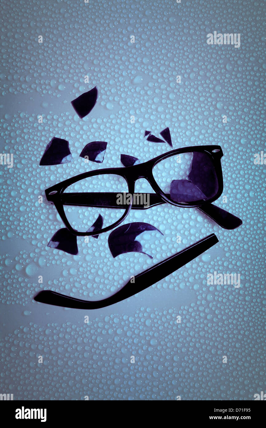 broken sunglasses on a wet table - Stock Image