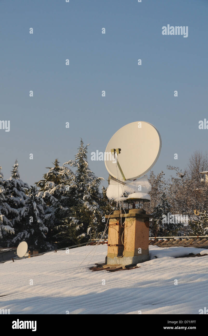Satellite dish, antenna on the roof in winter. Stock Photo
