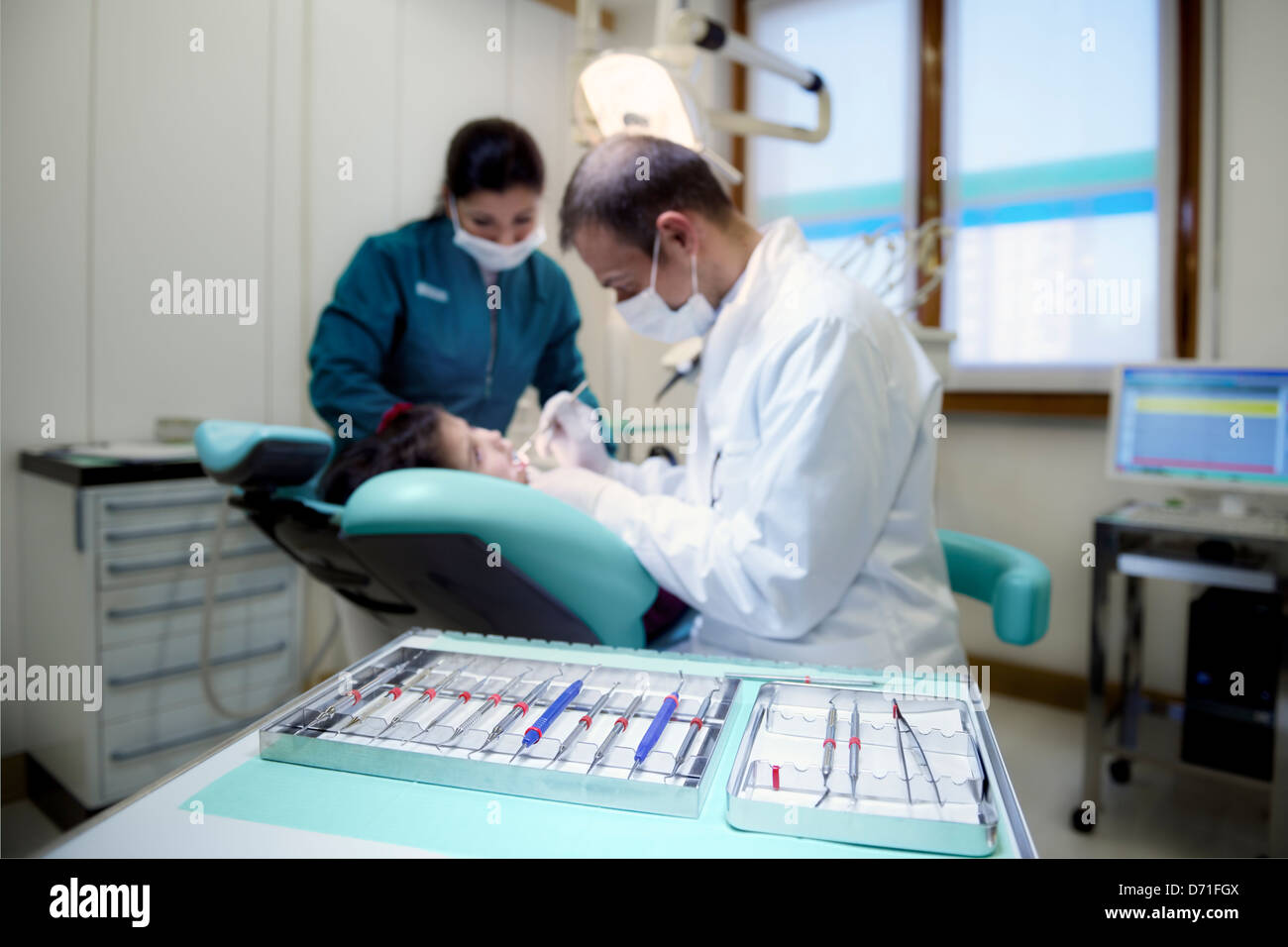 Close up of dental equipment in hospital with patient lying on couch and dentist working. Focus on foreground - Stock Image