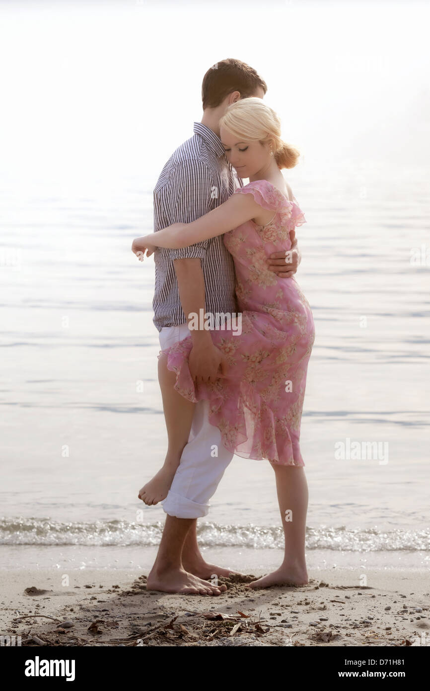 a couple on the beach, hugging each other Stock Photo