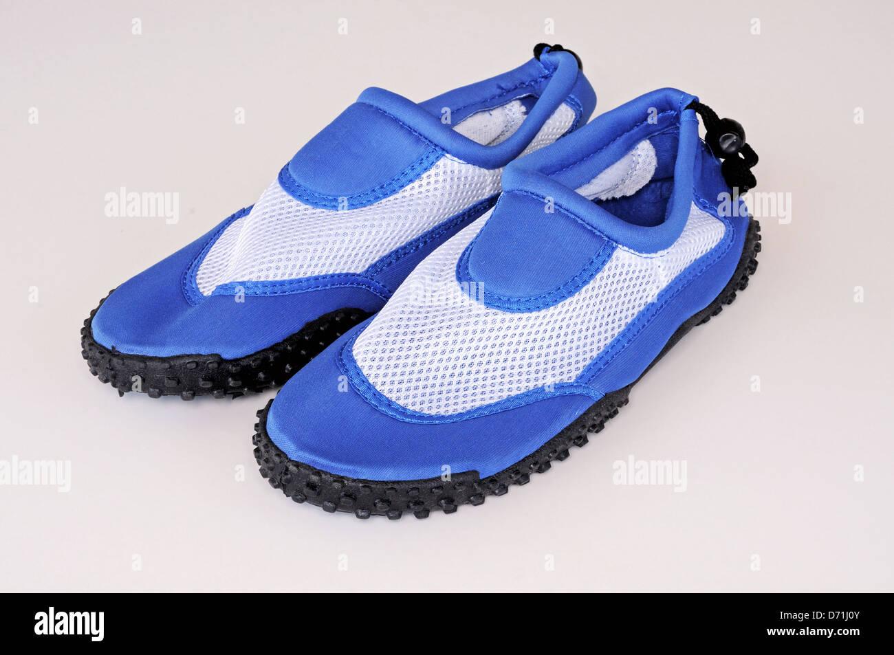 Gents blue beach shoes against a plain background. - Stock Image