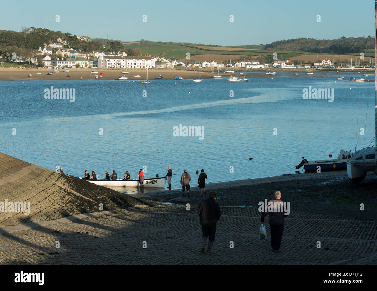 Appledore, North Devon, England. A rowing team is embarking from clinker rowing gig on the river Torridge. - Stock Image