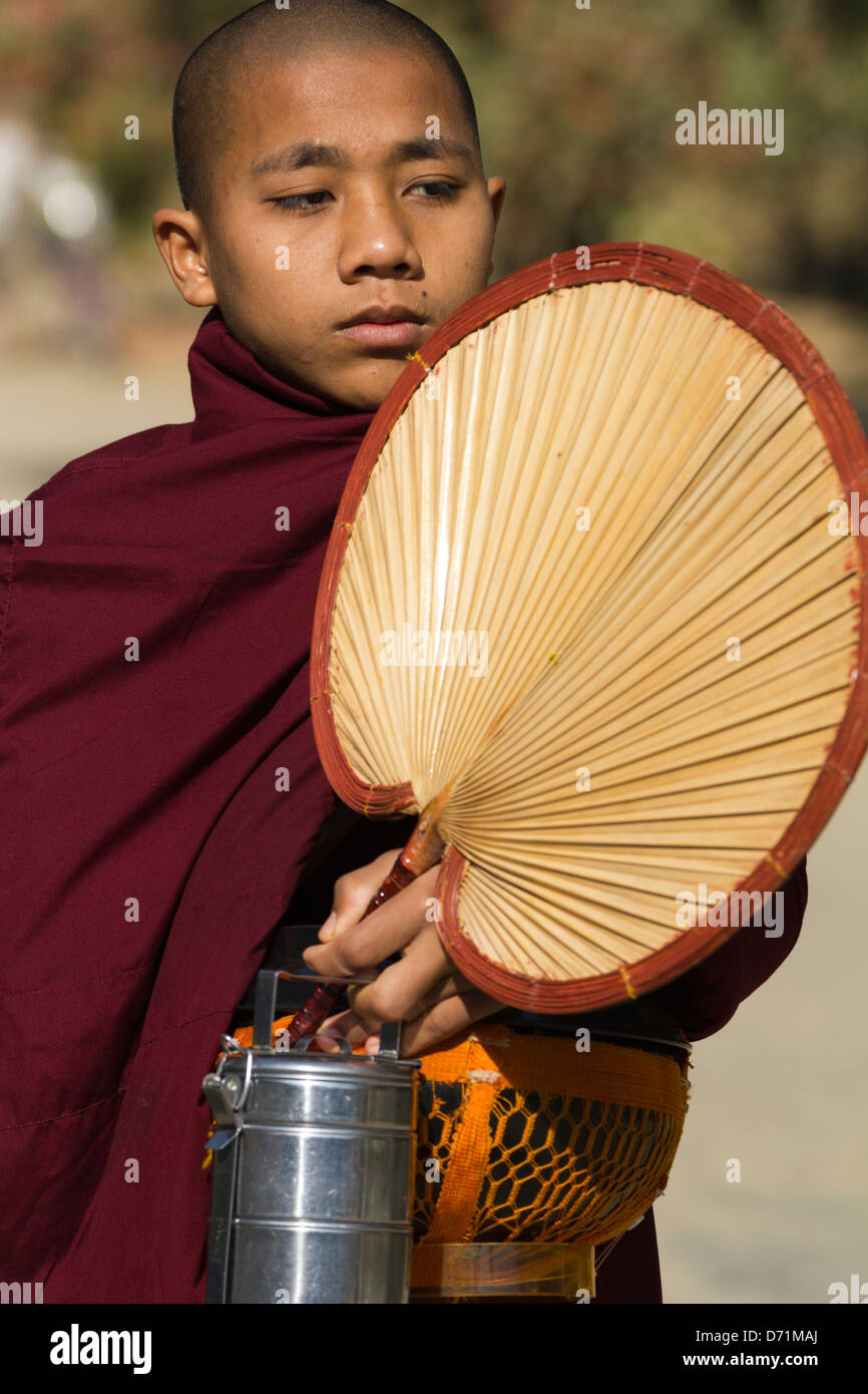 Novice monk with fan, lunchbox and collection bowl in Bagan, Myanmar Stock Photo