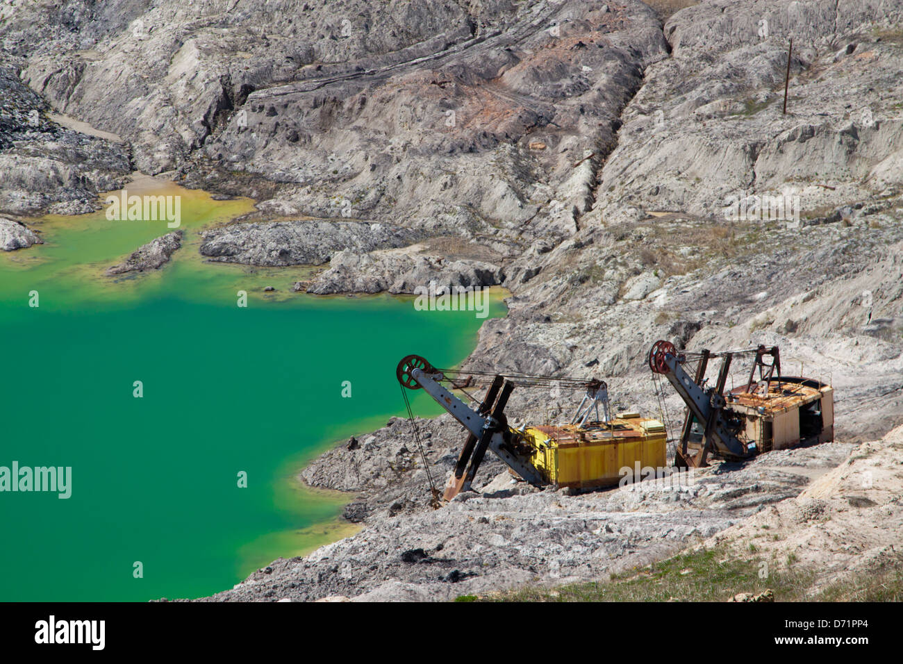 Earth movers beside a groundwater lake in the Chokurovo Coal Mine, an open pit mine in Bulgaria where Lignite is - Stock Image