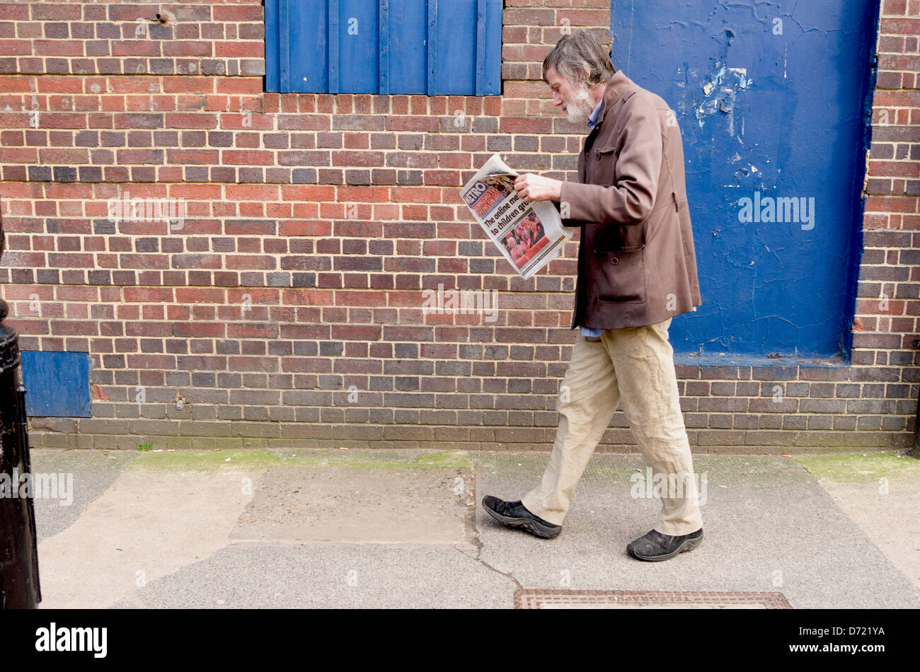 Man walking whilst reading a newspaper. Stock Photo