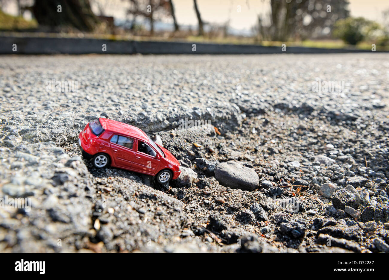 Miniature car in blow hole on the street, symbolic photo street damages Stock Photo