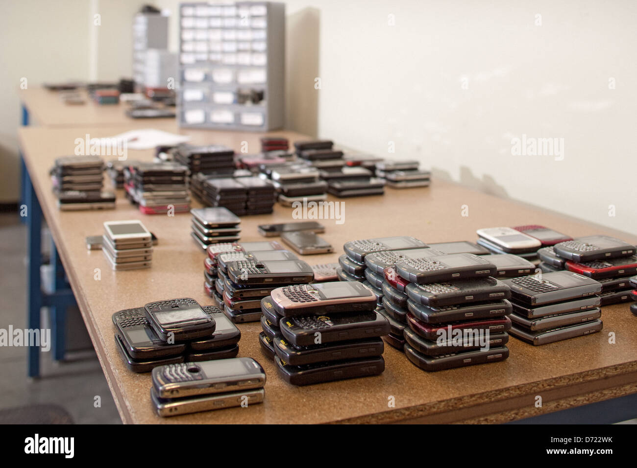 Stacks of cell phones ready to be tested in a electronics recycling center. - Stock Image