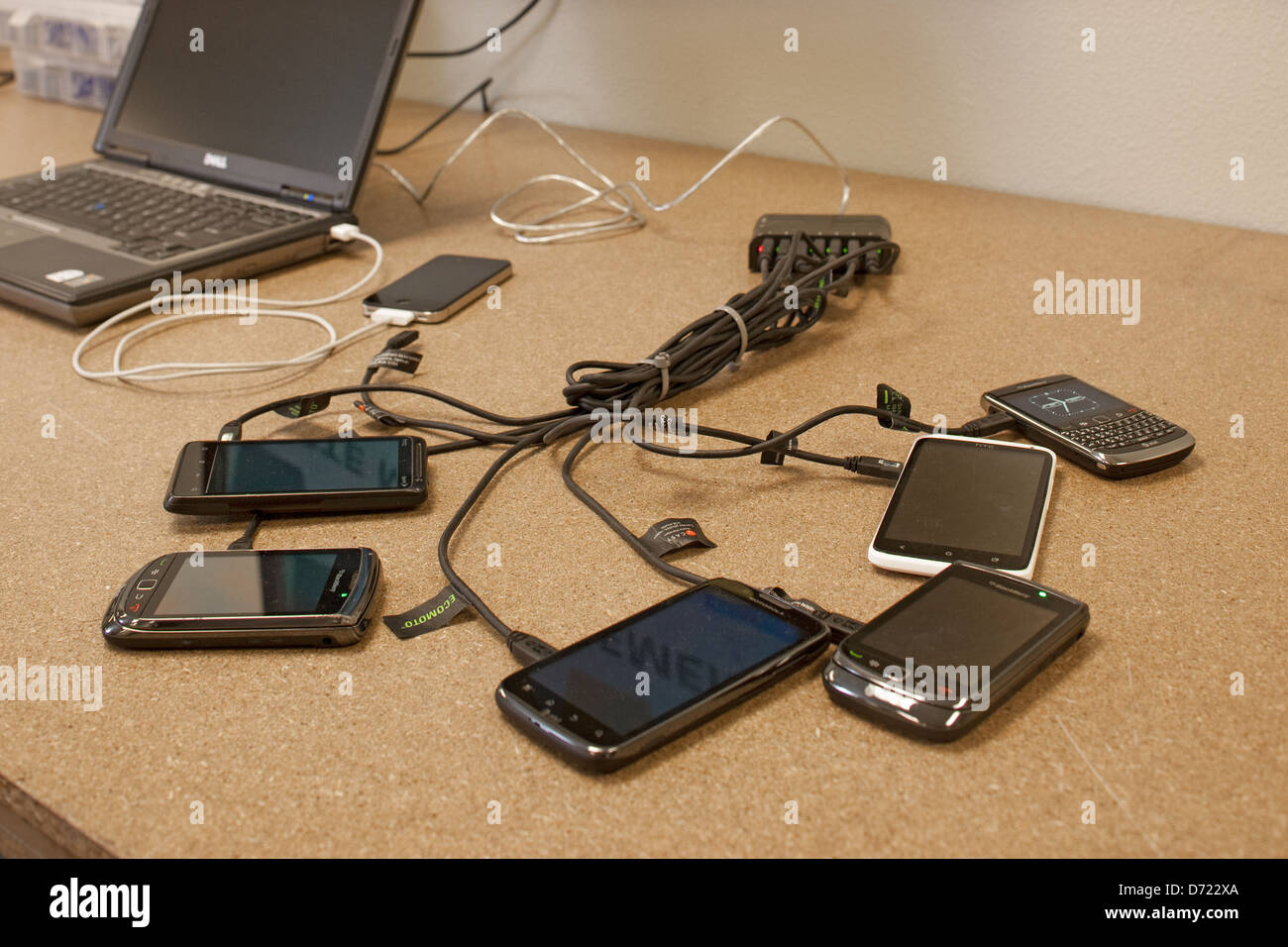 Cell phone testing and charging station at electronics recycling center. - Stock Image