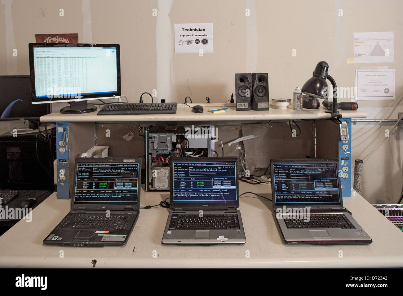 Testing recycled laptops to refurbish for resale. - Stock Image