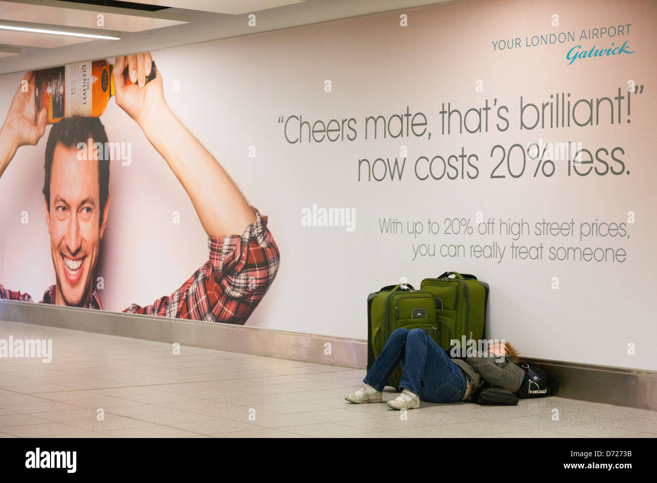 A passenger asleep next to suitcases and underneath a duty free advertisement in Gatwick Airport departures - Stock Image
