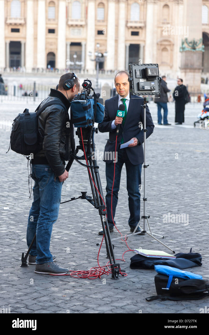 Reporters filming in St. Peter's Square the day after the resignation of Pope Benedict XVI (L) - Stock Image