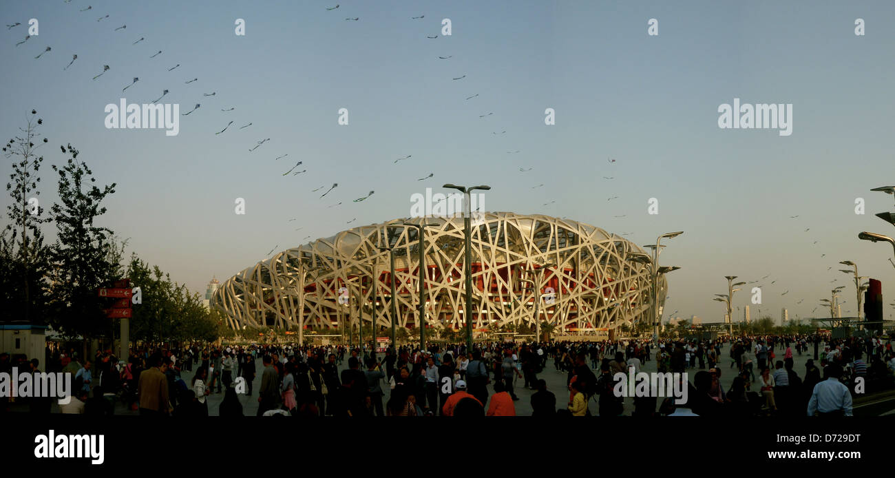 Crowds of people and kites flying outside the Birds Nest stadium in Beijing, China - Stock Image