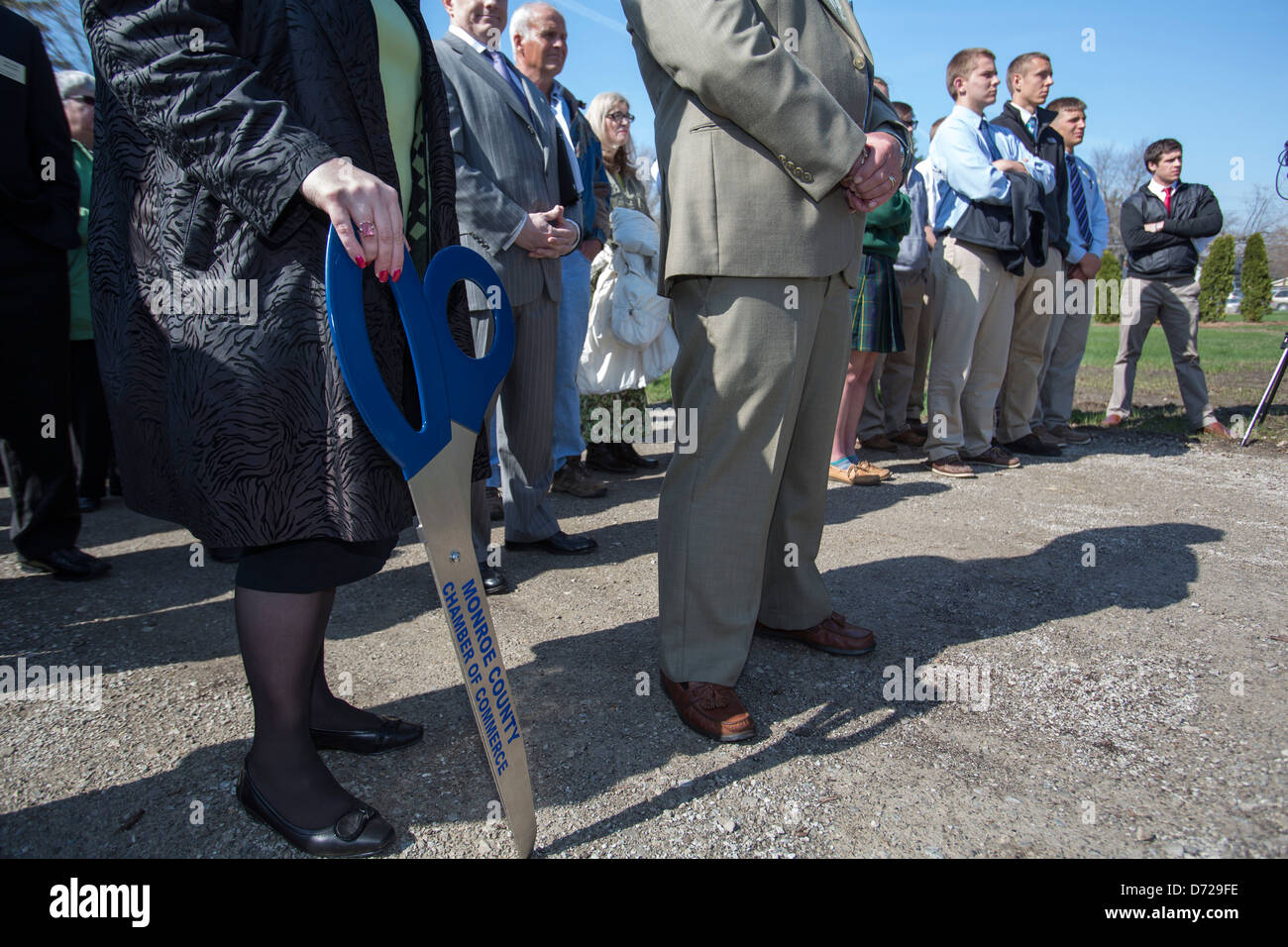 A representative of the Chamber of Commerce holds oversized scissors for a ribbon-cutting ceremony at a solar power - Stock Image