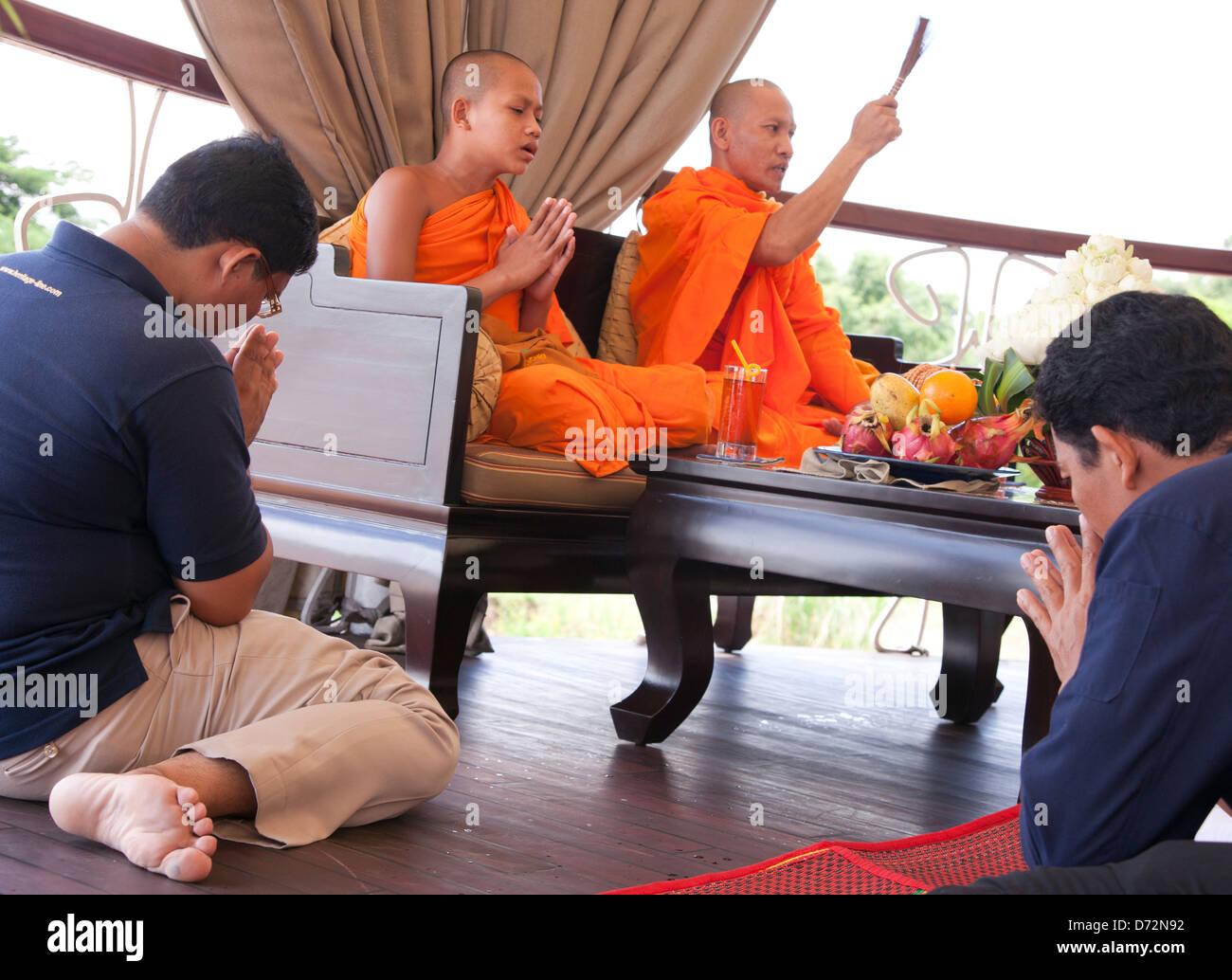 Phnom Penh, Cambodia, Buddhist monk blesses the crew of the vessel flow Jayavarman - Stock Image
