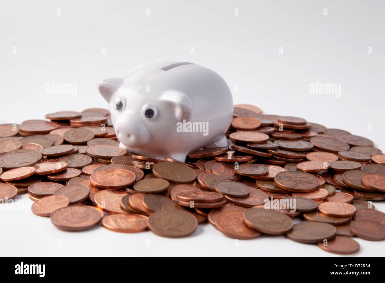 Piggy bank and pennies on white background - Stock Image