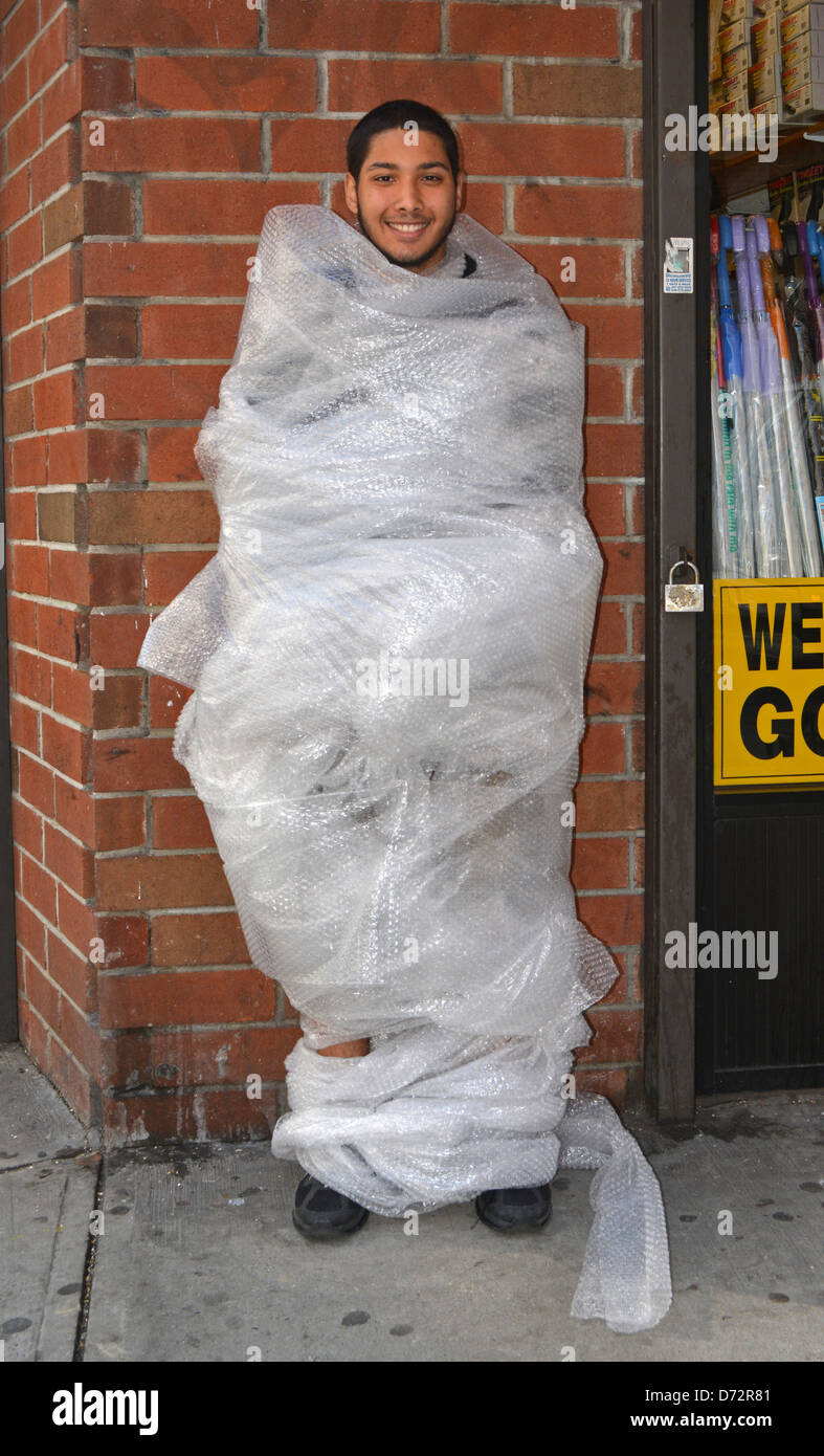 Young man wrapped in bubble wrap as part of a psychology experiment at New York University. In the East Village, - Stock Image