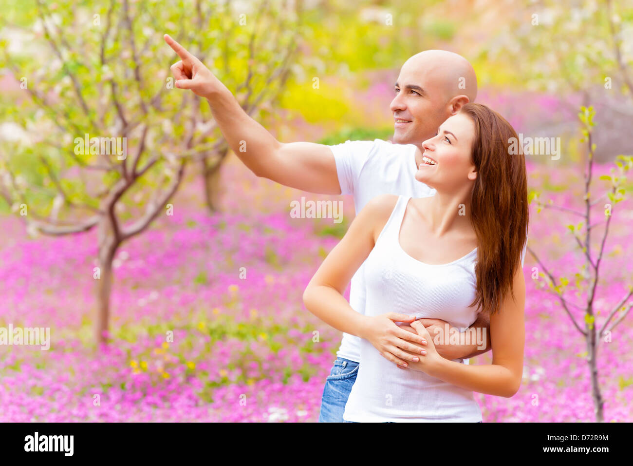 Attractive guy showing something in sky his lovely girlfriend, having fun in spring park, relaxation outdoors, romantic - Stock Image