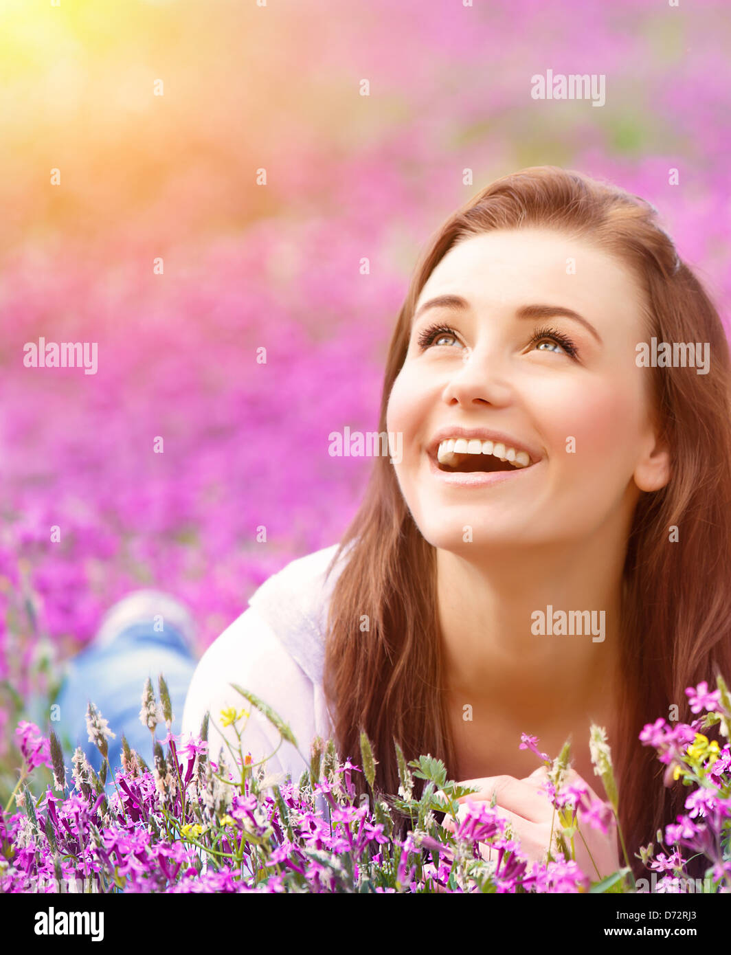 Closeup portrait of beautiful female laying down in fresh pink floral field, warm sunset light, spring nature - Stock Image