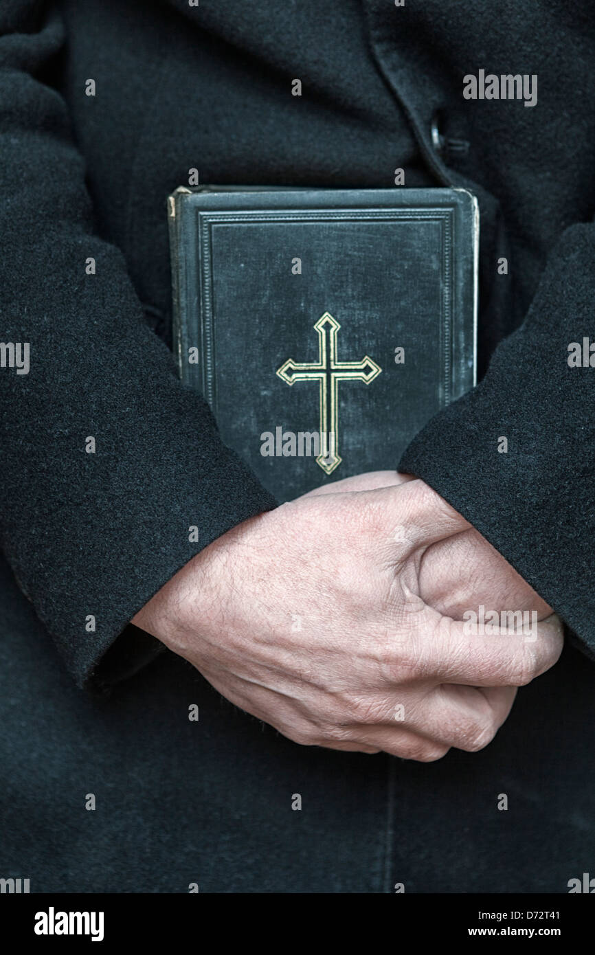 Priest with a bible-close-up Stock Photo
