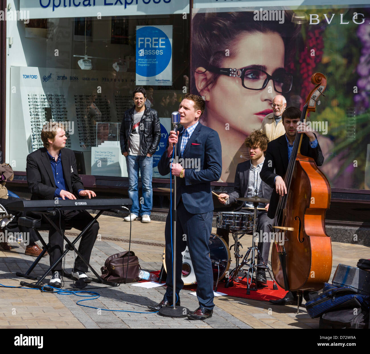 Live group busking to shoppers on a Saturday morning, Briggate, Leeds, West Yorkshire, UK - Stock Image