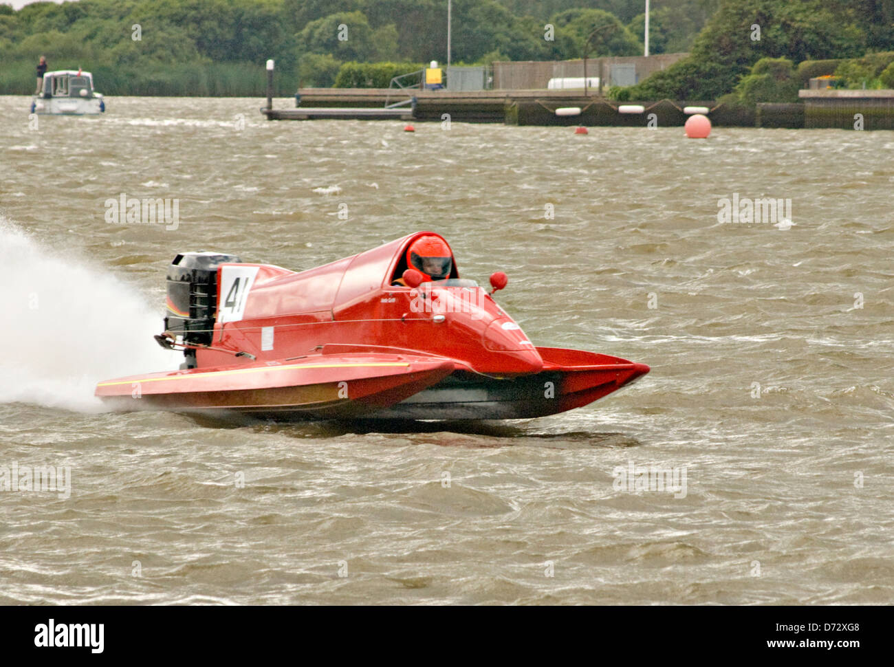 Red racing boat, speeding along on lake, water spray coming from back. Overcast sky. - Stock Image