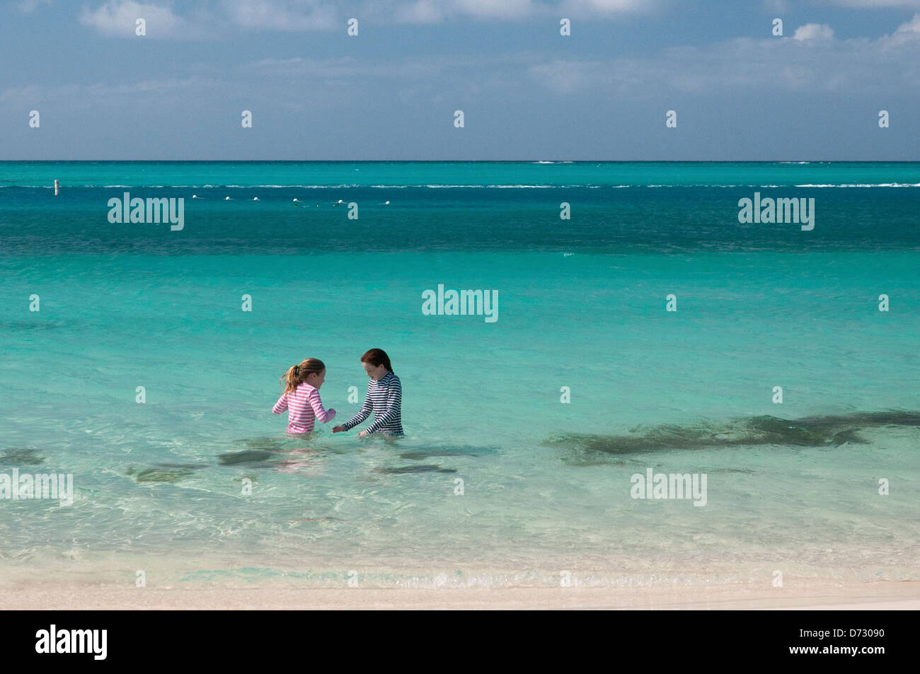 Sisters playing in Grace Bay at Providenciales, Turks and Caicos - Stock Image
