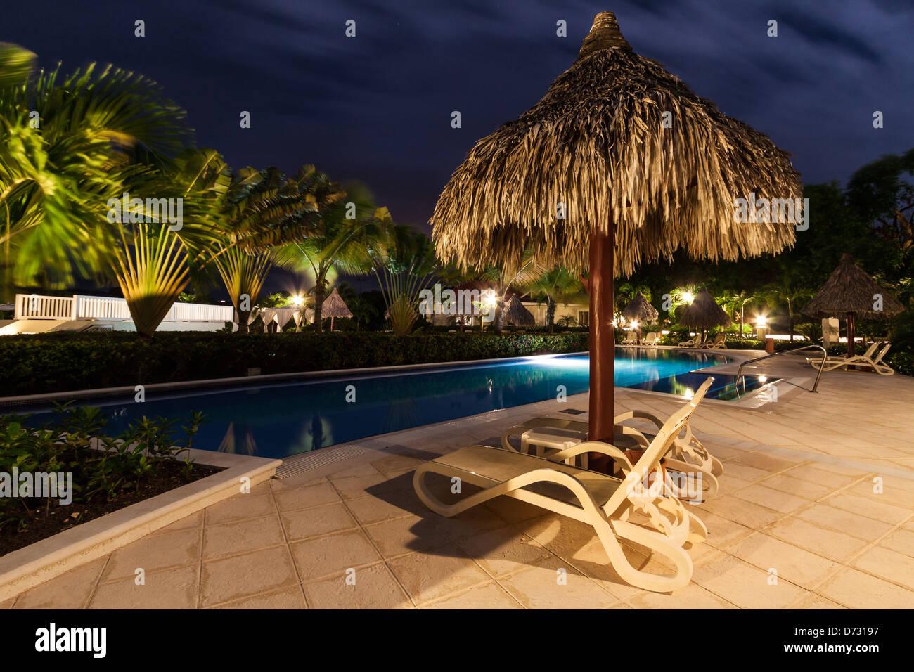 Straw umbrella and two beach seats near an illuminated pool by night - Stock Image