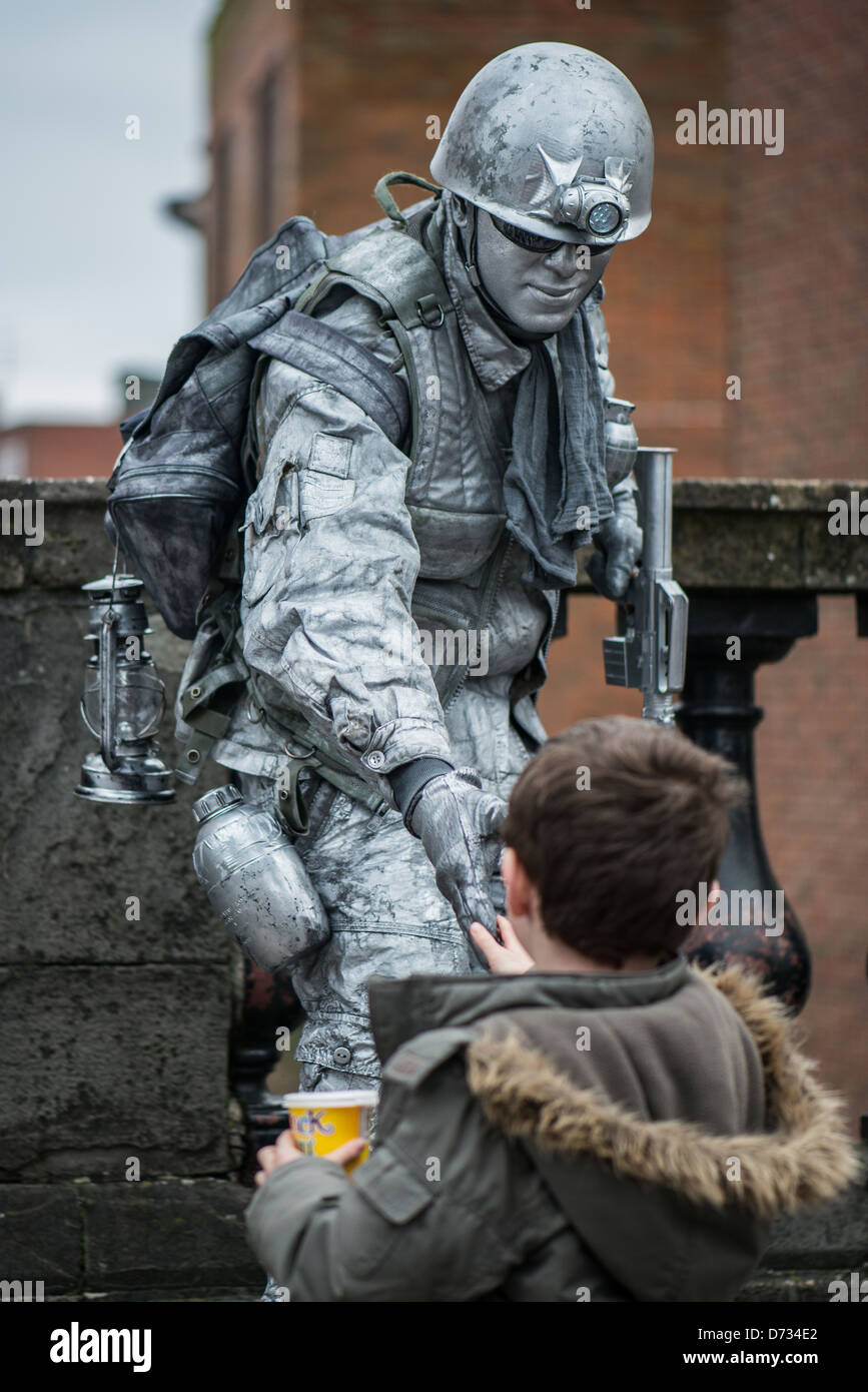 Statue man as soldier meets boy - Stock Image