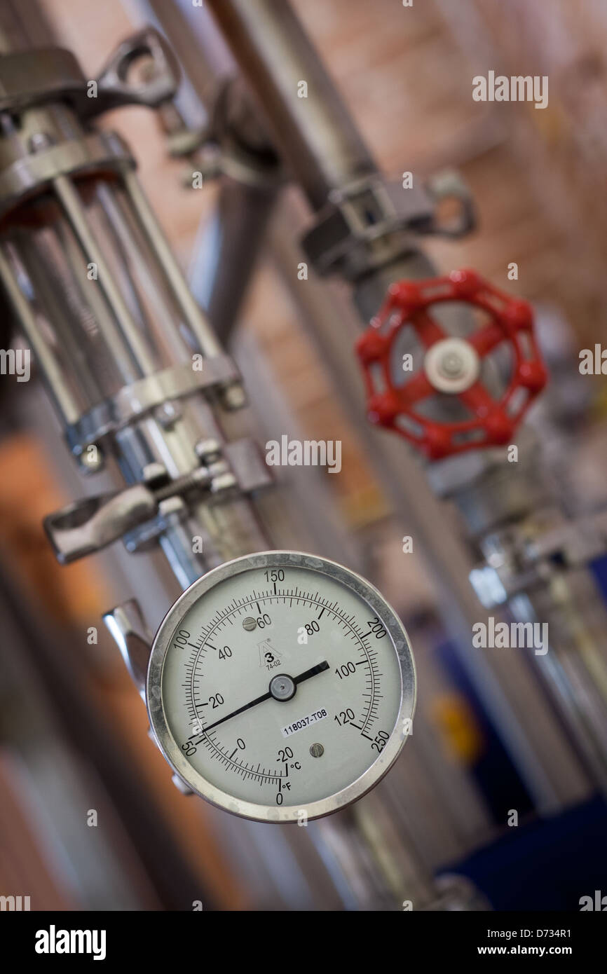 Temperature guage attached to stainless steel pipework with red valve in background - Stock Image