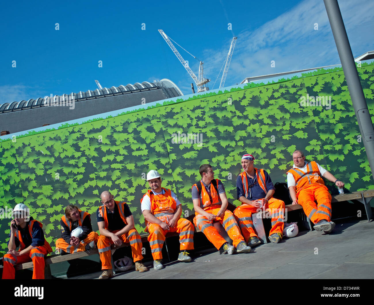 Seven workers wearing orange high visibilty saftey clothing taking a break on Kings Boulevard, Kings Cross, London - Stock Image